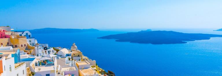 Der Blick über den Küstenort Oia auf Santorin zeigt strahlend weiße Häuser und das tief blaue Mittelmeer.
