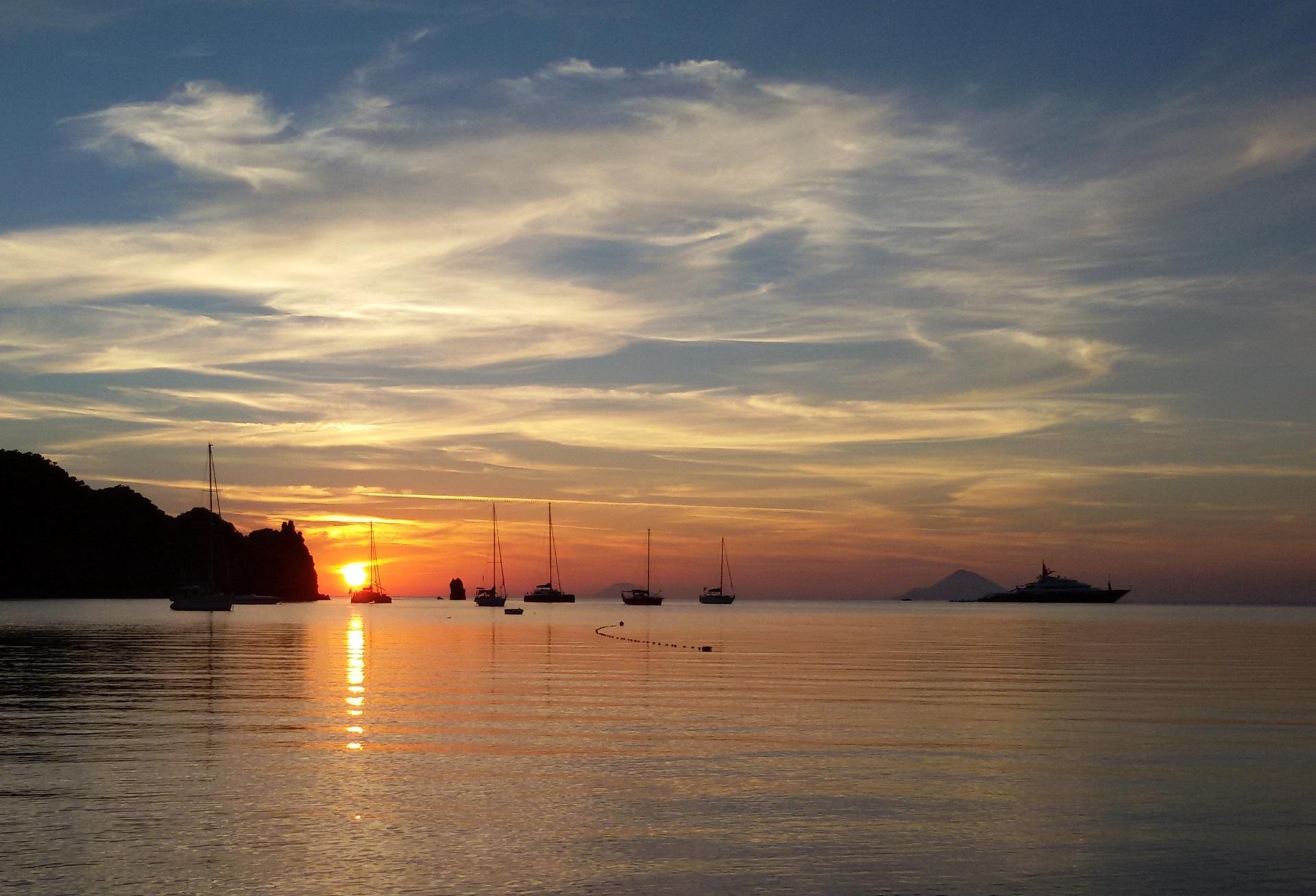 Zu sehen ist der tiefrote Sonnenuntergang über den Liparischen Inseln am Horizont und den Booten, die auf dem ruhigen Meer ankern.