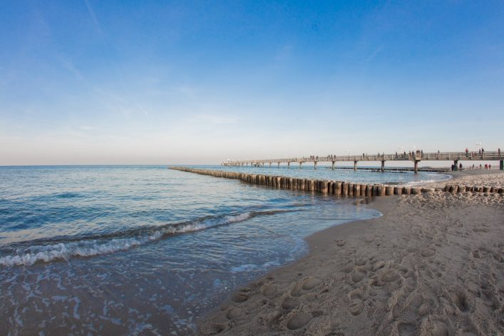 beach with Pier of kuehlungsborn at the baltic sea on a beautiful day with blue sky shutterstock_567243244