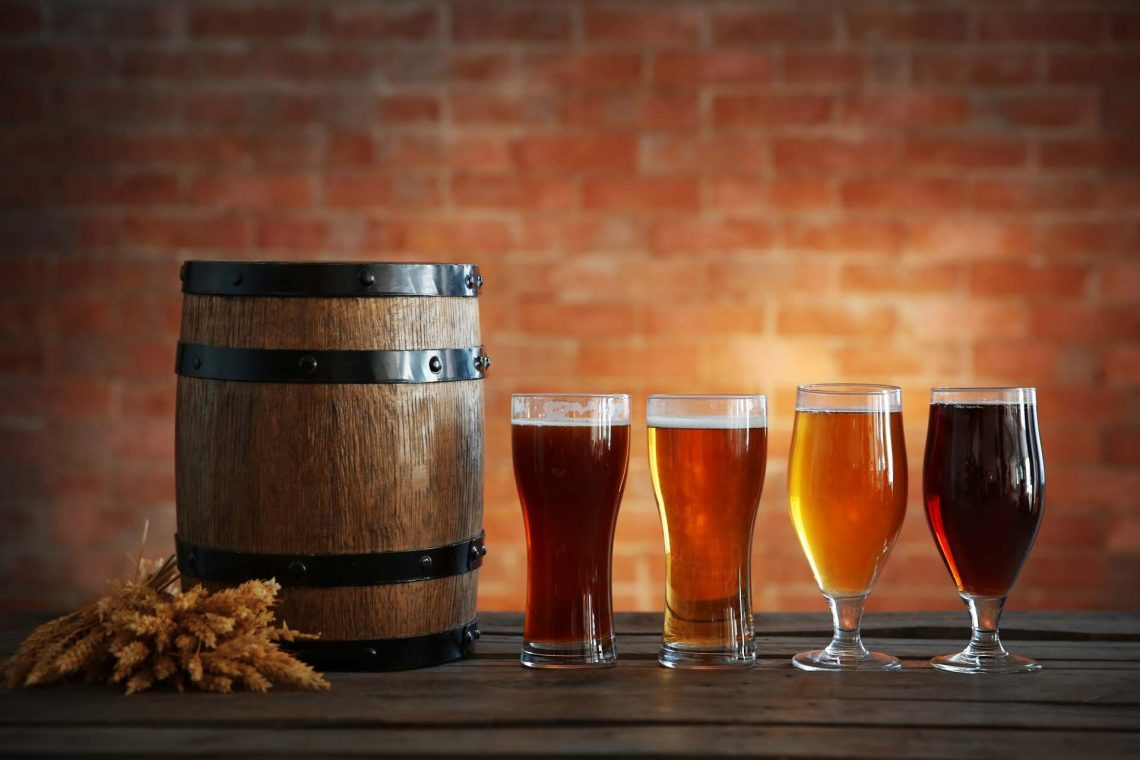 shutterstock_399989320_Glasses with different sorts of craft beer, wooden barrel and barley ears on brick wall background_klein