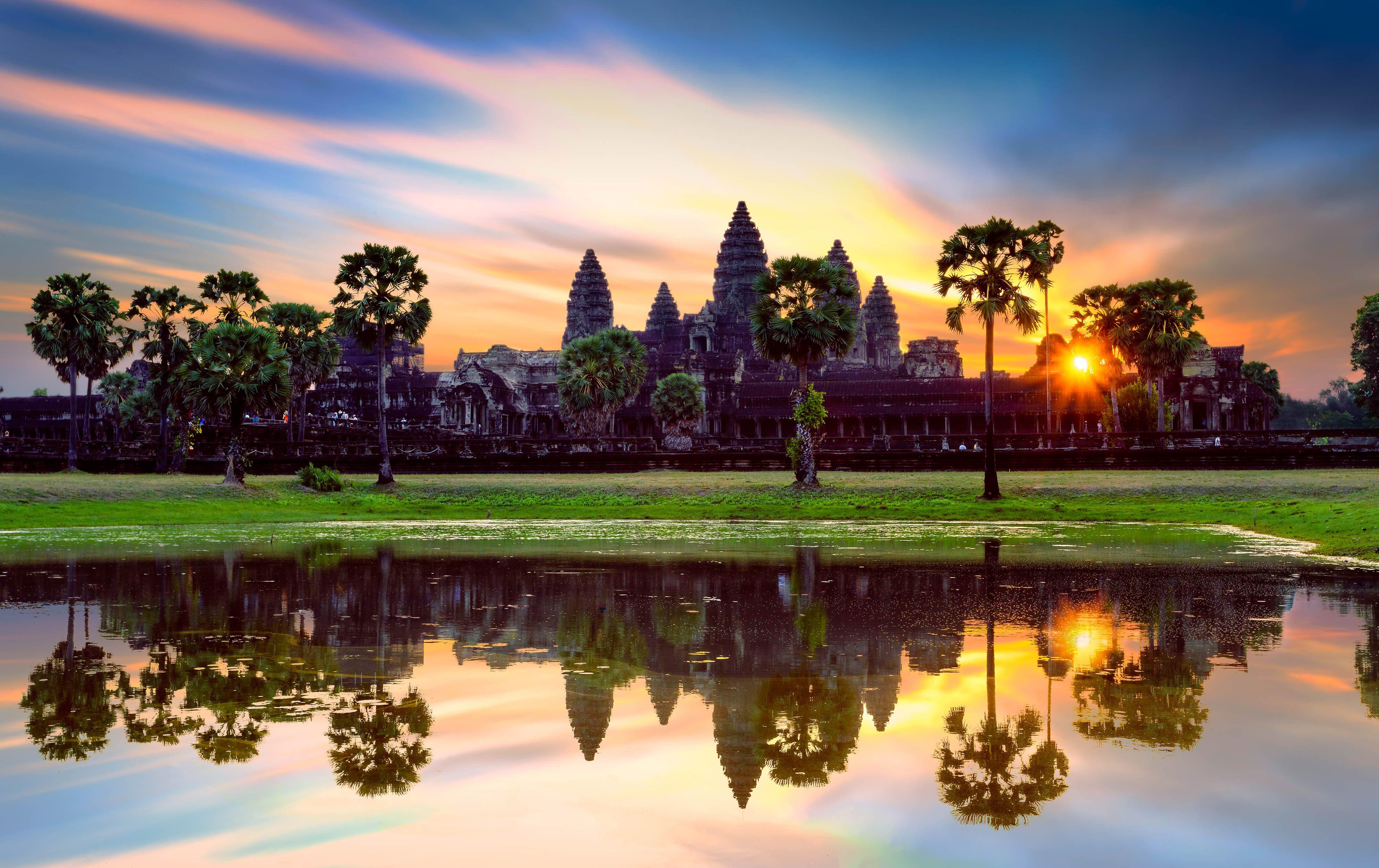 Der Tempel Angkor Wat in Kambodscha spiegelt sich bei Sonnenaufgang im Wasser wider.