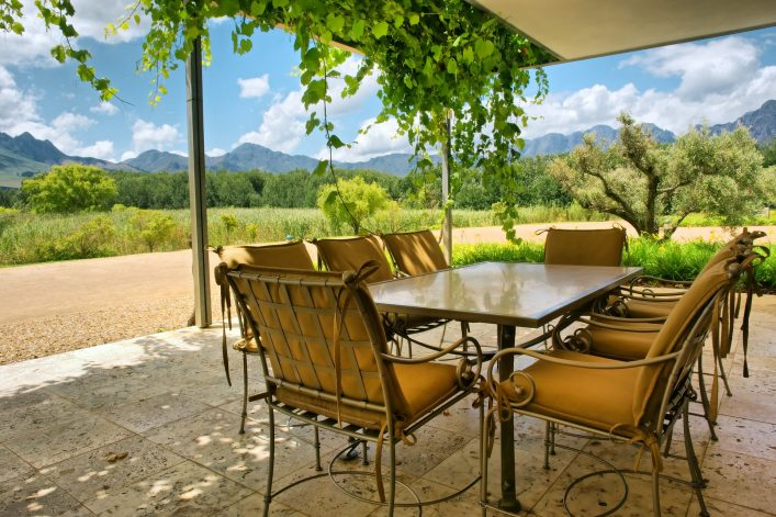 Table in vine-covered pavillion next to magnificent mountains. Shot near Stellenbosch and Cape Town, South Africa. shutterstock_134720093