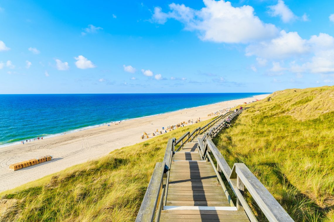 Wooden walkway along a coast of North Sea and view of beautiful beach near Wenningstedt village, Sylt island, Germany shutterstock_617961374_mini