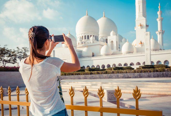 Eine Urlauberin fotografiert eine Moschee in Abu Dhabi
