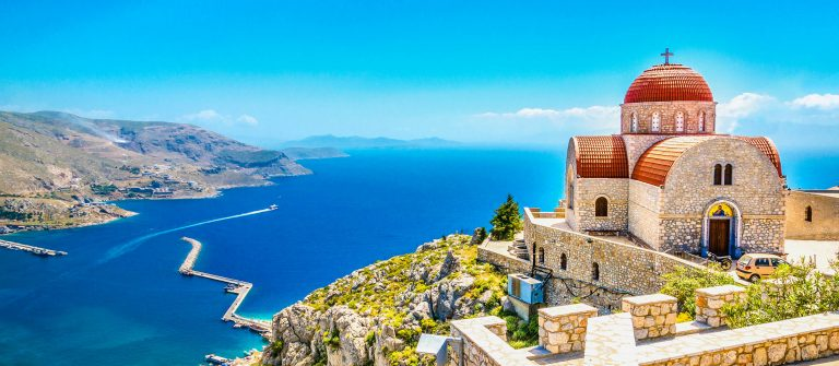 Remote church with red roofing on cliff, Greece