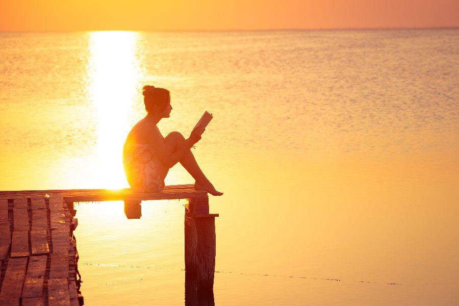 Frau sitzt während dem Sonnenuntergang auf dem Pier und liest ein Buch.