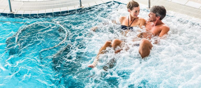 Couple in thermal wellness spa on water massage enjoying the treatment shutterstock_307058501-2 – Kopie