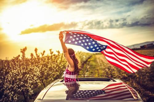 Girl Through a Car Sunroof Waving with USA Flag iStock_93831847_XLARGE-2